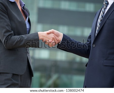Businessman and businesswoman handshake showing trust and friendship - stock photo