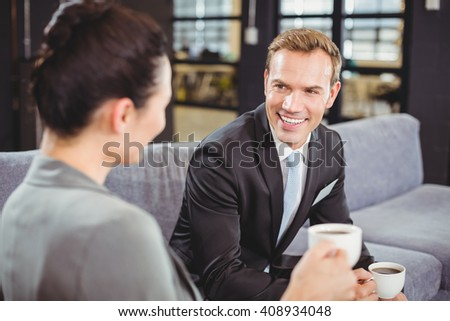 Businessman and businesswoman having a discussion during breaktime in office - stock photo