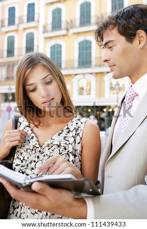 Businessman and businesswoman having a meeting outdoors, in a classic city, and looking at paperwork.