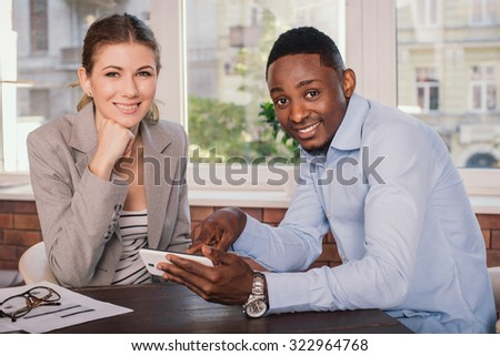 Businessman and businesswoman having meeting in office. Young business people discussing something and showing this using mobile phone