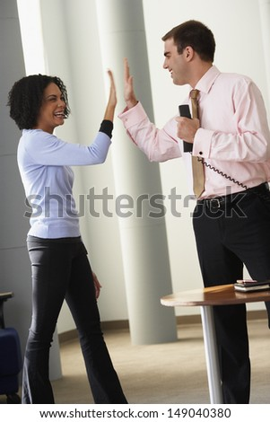 Businessman and businesswoman high-fiving - stock photo