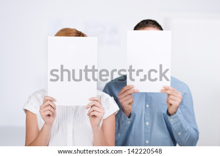 Businessman and businesswoman holding blank paper in front of their faces in office