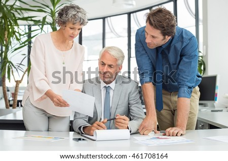 Businessman and businesswoman in a discussion during meeting in a board room. Senior businesswoman showing report to staff. Business partners working together on a new project.