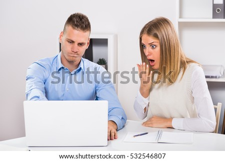 Businessman and businesswoman in panic are using laptop and working at their office.Worried businessman and businesswoman in panic looking at laptop