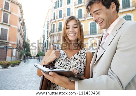 Businessman and businesswoman laughing while having a meeting outdoors, in a classic city.