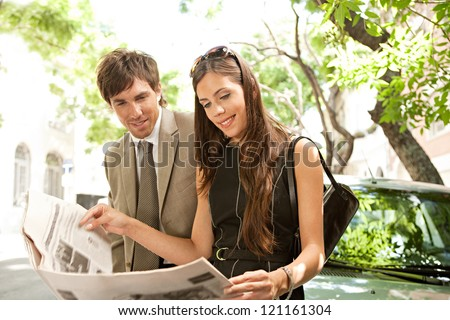 Businessman and businesswoman leaning together on a parked car and sharing a newspaper in a tree aligned street in a classic city. - stock photo