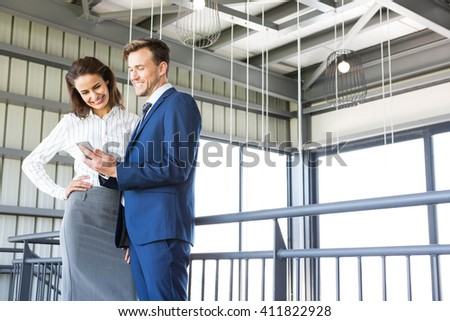 Businessman and businesswoman looking at smartphone in office - stock photo