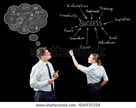Businessman and businesswoman on a background of black wall. Drawing ideas. Creative background.
