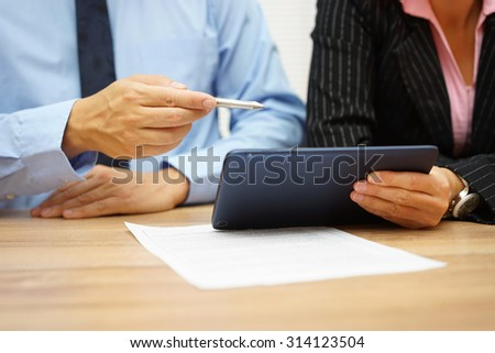 businessman and businesswoman  on meeting discussing about data on tablet pc and document - stock photo