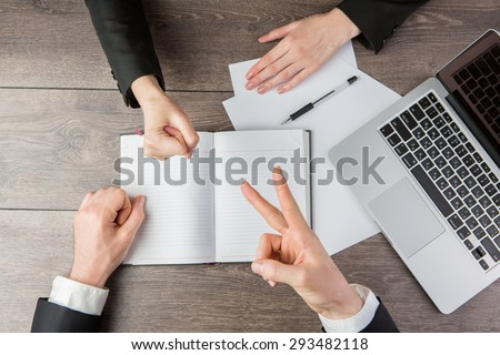 Businessman and businesswoman playing Rock-paper-scissors during the negotiations. Solution controversial conflicts. Top view.  White paper, where you can place your text or information - stock photo