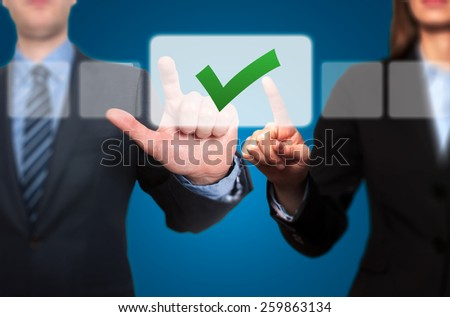 Businessman and Businesswoman pressing Button and Ticking Check Box - stock photo