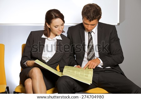 Businessman and businesswoman reading newspaper at waiting room - stock photo