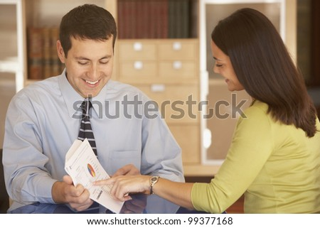 Businessman and businesswoman reading over paperwork