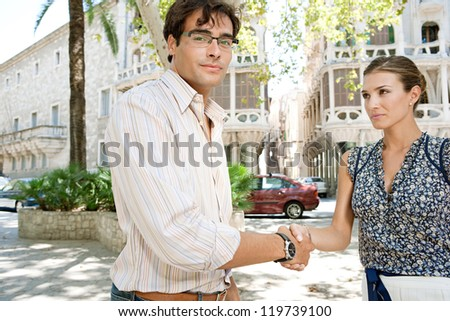 Businessman and businesswoman shaking hands in business agreement while standing near office buildings in a classic city. - stock photo