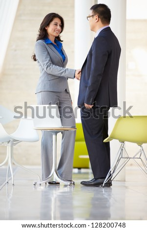 Businessman And Businesswoman Shaking Hands In Modern Office - stock photo