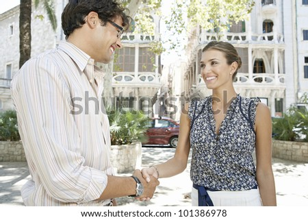Businessman and businesswoman shaking hands in the city, smiling.