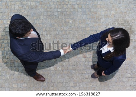 Businessman and businesswoman shaking hands outdoors