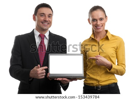 businessman and businesswoman showing a laptop with blank screen - stock photo