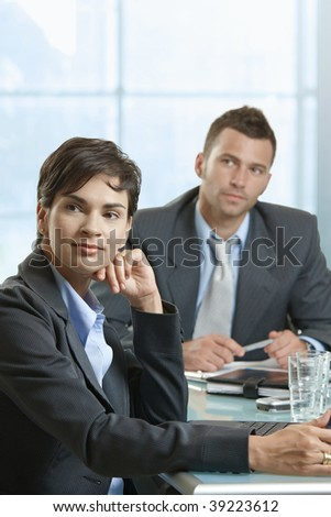 Businessman and businesswoman sitting at desk in meeting room, looking to somebody.