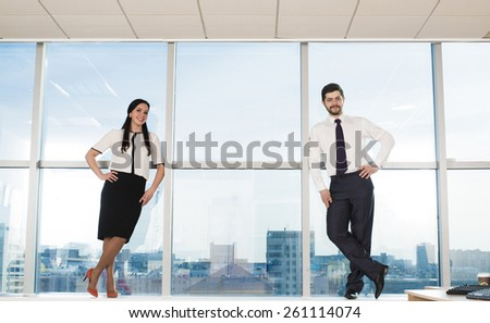 Businessman and businesswoman stand full length on floor near modern office window against urban view big city center houses on background Man and woman wear black white well formal business dress  - stock photo