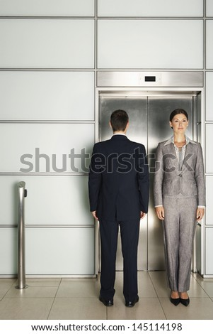 Businessman and businesswoman standing in front of elevator in office - stock photo