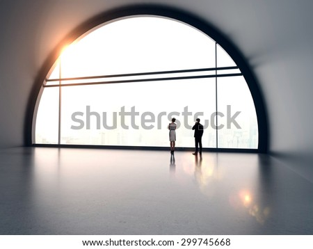 businessman and businesswoman standing in futuristic office - stock photo
