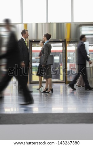 Businessman and businesswoman standing while coworkers walking around them in office - stock photo