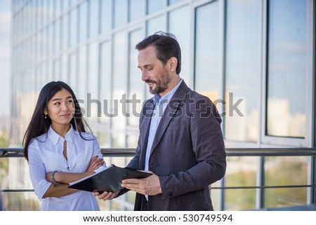 Businessman and businesswoman talking about documentation for new business foreign company while working outdoors in office interior.