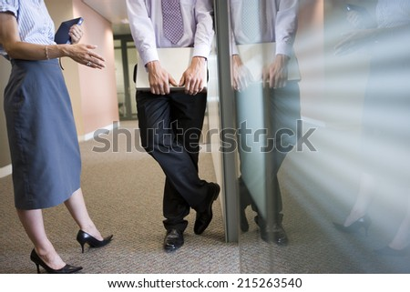Businessman and businesswoman talking in corridor beside office window, low section, side view - stock photo