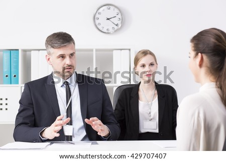 Businessman and businesswoman talking with young woman during job interview