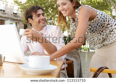 Businessman and businesswoman using a laptop computer while at a coffee shop terrace table outdoors in a classic city. - stock photo