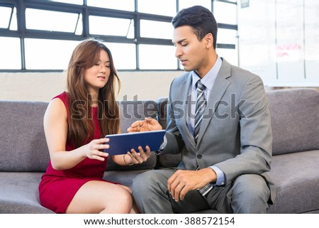 Businessman and businesswoman using digital tablet in the office - stock photo