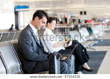 businessman and businesswoman using laptop and tablet computer at airport - stock photo