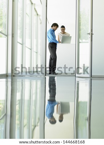 Businessman and businesswoman using laptop in meeting viewed through open office door - stock photo