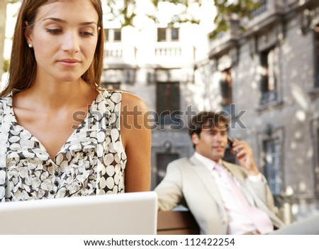 Businessman and businesswoman using technology while sitting on wooden benches in a classic city square.