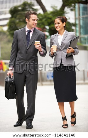 Businessman And Businesswoman Walking Along Street Holding Takeaway Coffee - stock photo