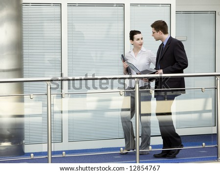 Businessman and businesswoman walking and talking on modern office corridor. - stock photo