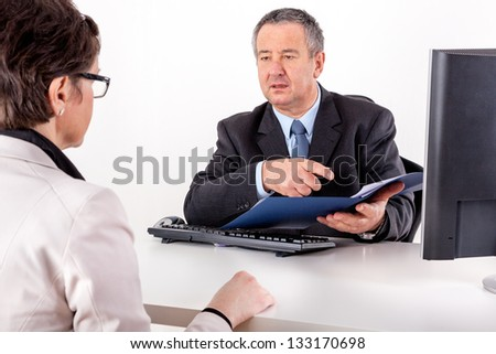 Businessman and businesswoman with documents in the office
