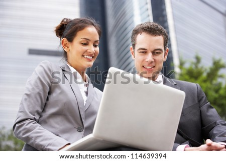 Businessman And Businesswoman Working On Laptop Outside Office - stock photo