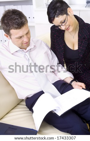 Businessman and businesswoman working together, stitting on sofa looking at financial figures, smiling.