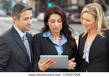 Businessman And Businesswomen Using Digital Tablet Outside - stock photo