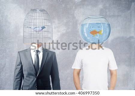 Businessman and casually dressed man with fishtank and birdcage instead of heads on concrete background, 3D Rendering - stock photo