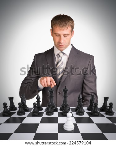 Businessman and chess board with chess. Gray background. Business concept