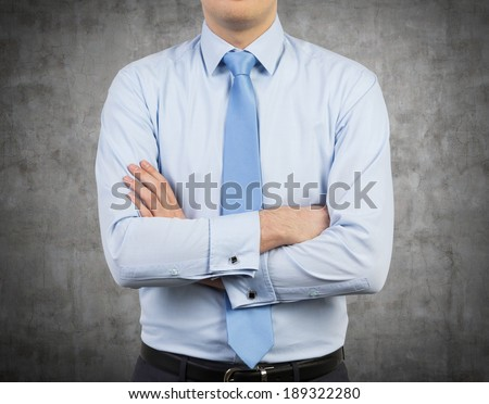 Businessman and crossed hands, concrete wall. - stock photo