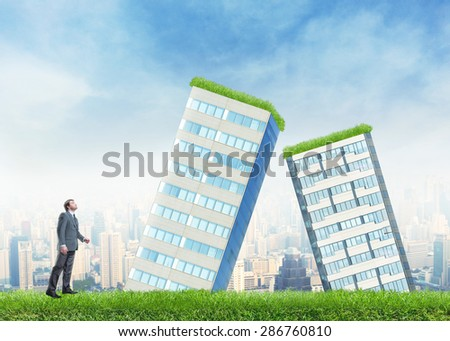 Businessman and falling buildings - stock photo