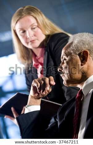 Businessman and female assistant in a boardroom meeting - stock photo