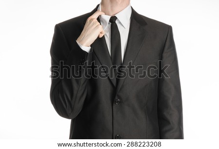 Businessman and gesture topic: a man in a black suit and tie holding a hand to his shirt collar isolated on a white background in studio