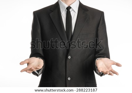 Businessman and gesture topic: a man in a black suit and tie holding hands in front isolated on white background in studio