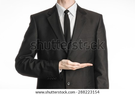 Businessman and gesture topic: a man in a black suit and tie holding his hand in front of him isolated on a white background in studio