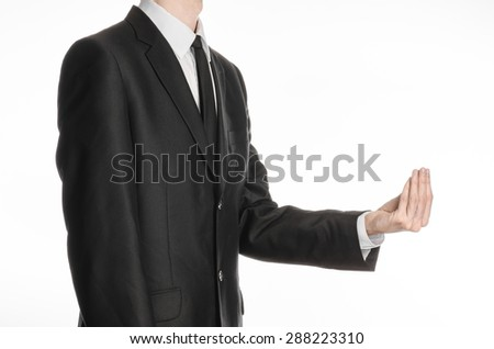 Businessman and gesture topic: a man in a black suit and tie holding his hand in front of him and shows a pinch gesture on an isolated white background in studio - stock photo
